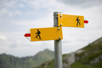 Close-up of hiking signs at Swiss Alps against sky