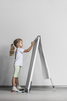 Side view of girl drawing on flipchart against white wall