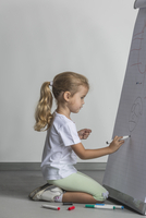 Side view of girl kneeling while drawing on flipchart against white wall