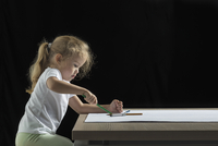 Side view of girl drawing on paper at table against black background