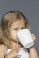 Cute girl drinking coffee against gray background