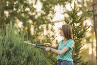 Young woman cutting plants with pruning shears at yard