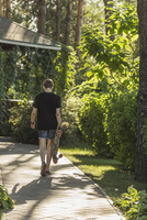 Rear view of man carrying skateboard while walking on footpath at park