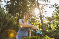 Young woman cutting plants at yard