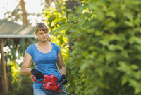 Woman cutting plants with hedge clipper at yard