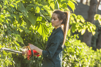 Side view of woman cutting plants with hedge clipper at yard