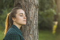 Beautiful woman with eyes closed leaning on tree trunk at park