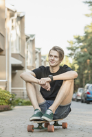 Thoughtful young man sitting on skateboard outdoors