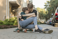 Happy young couple embracing while sitting on skateboard outdoors
