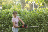 Woman trimming plants with hedge clipper at yard