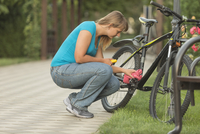 Side view of woman repairing bicycle in park