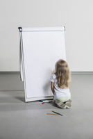 Rear view of girl drawing on flipchart against white wall
