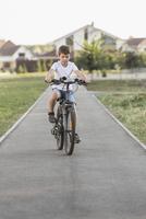 Boy cycling on footpath