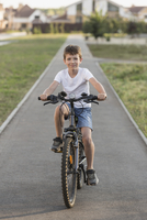 Portrait of boy cycling on footpath