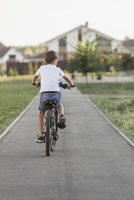 Rear view of boy cycling on footpath