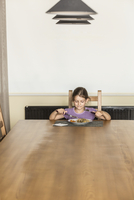 Girl having food at dining table in house