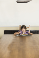 Portrait of girl eating food at dining table in house