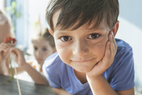 Close-up portrait of cute boy leaning on table at home
