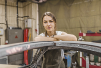 Portrait of confident female mechanic leaning on car at garage