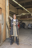 Portrait of confident female mechanic standing arms crossed at garage