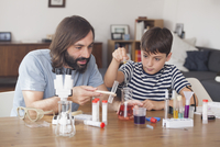 Father and son working on science experiment at home 11016031626| 写真素材・ストックフォト・画像・イラスト素材|アマナイメージズ