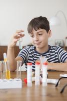 Happy boy holding test tube at home 11016031627| 写真素材・ストックフォト・画像・イラスト素材|アマナイメージズ