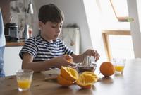 Boy making orange juice at table in house