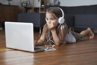 Girl using laptop while listening to music on hardwood floor