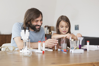 Father and daughter working on science project at home 11016031632| 写真素材・ストックフォト・画像・イラスト素材|アマナイメージズ