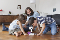 Happy family looking at boy using microscope on hardwood floor