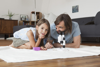 Father and daughter using microscope on carpet at home 11016031646| 写真素材・ストックフォト・画像・イラスト素材|アマナイメージズ