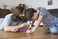 Father and son using microscope on hardwood floor 11016031648| 写真素材・ストックフォト・画像・イラスト素材|アマナイメージズ