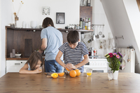Boy squeezing oranges while sister drinking juice with father in background at kitchen