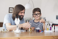 Father and son working on school science project at home