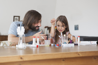 Father and daughter doing science experiment at home 11016031659| 写真素材・ストックフォト・画像・イラスト素材|アマナイメージズ