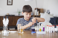 Boy concentrating on school science project at table