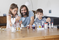 Father and children doing science experiment on table in house