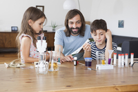 Happy father and children doing school science project at home