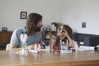 Father and daughter doing science experiment at table 11016031667| 写真素材・ストックフォト・画像・イラスト素材|アマナイメージズ