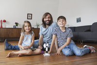Portrait of father and children with microscope sitting on floor at home 11016031671| 写真素材・ストックフォト・画像・イラスト素材|アマナイメージズ