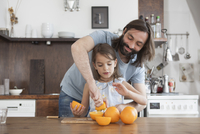 Father assisting daughter squeeze oranges in kitchen