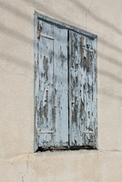 Low angle view of weathered wooden window on building