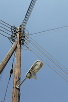 Low angle view of street light and electricity pylon against clear sky