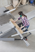 A female carpenter using a sliding table saw in a workshop
