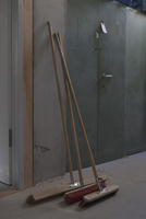 Brooms leaning against wall in workshop