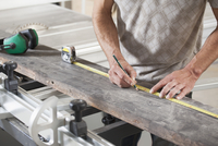 Midsection of male carpenter measuring plank on sliding table saw in workshop