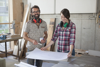Laughing male and female carpenters with blueprint in workshop