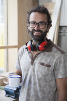 Portrait of happy mid adult carpenter having coffee in workshop