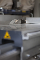 Close-up, surface level perspective of sliding table saw in workshop
