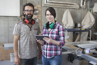 Portrait of confident carpenters with digital tablet in workshop